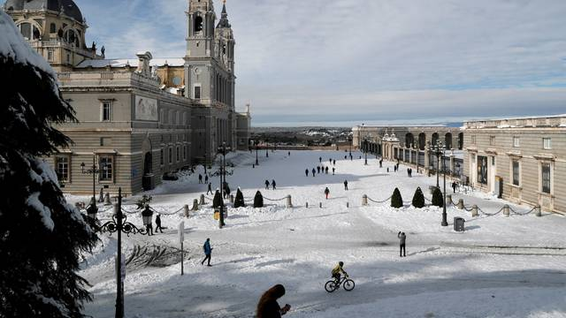 People walk in the snow outside La Almudena Cathedral in Madrid