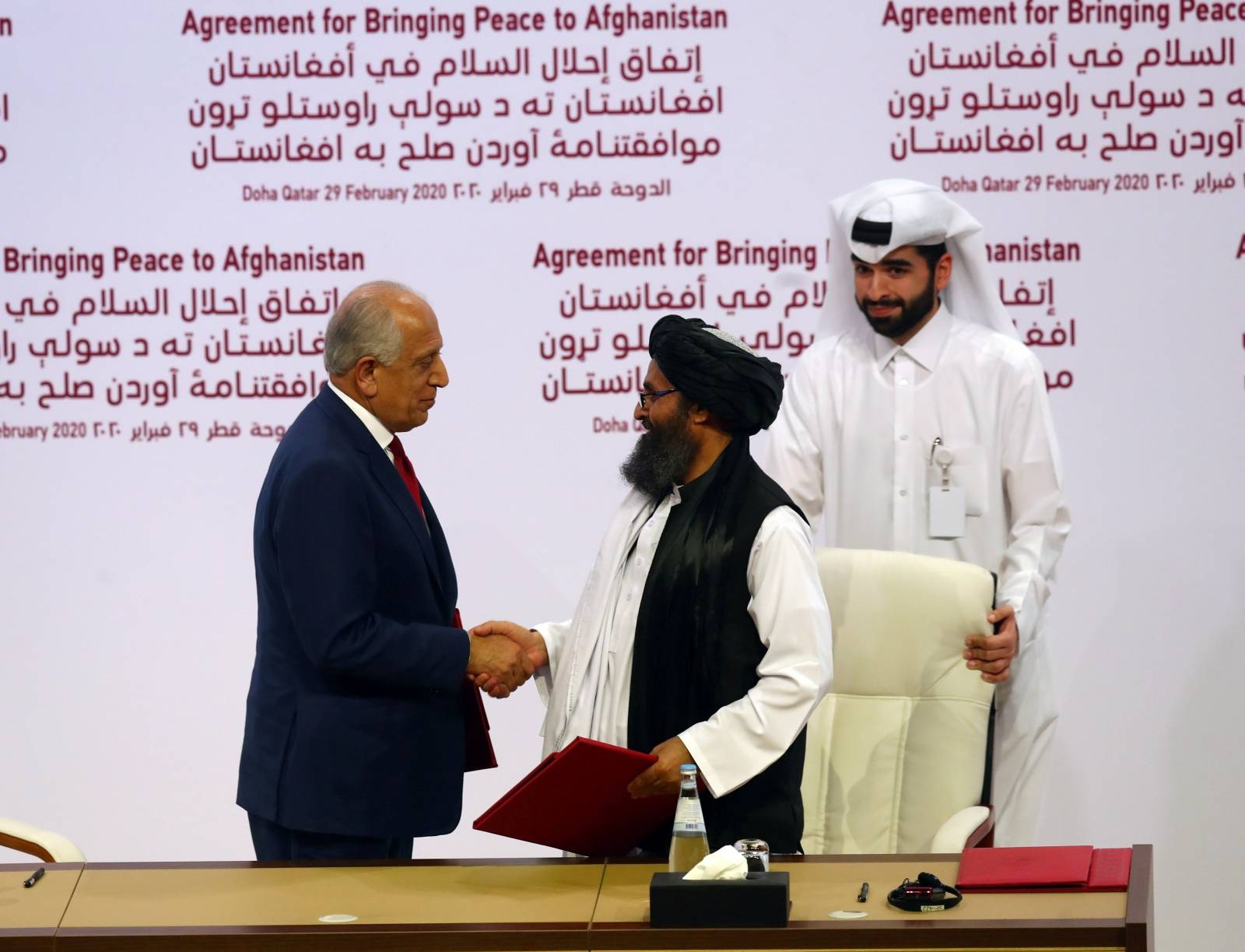 Mullah Abdul Ghani Baradar, the leader of the Taliban delegation, and Zalmay Khalilzad, U.S. envoy for peace in Afghanistan, shake hands after signing agreement at ceremony between members of Afghanistan's Taliban and the U.S. in Doha