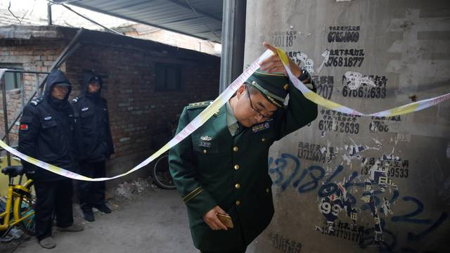 An investigator enters a house where a fire killed several people in Baiqiangzi village in Beijing