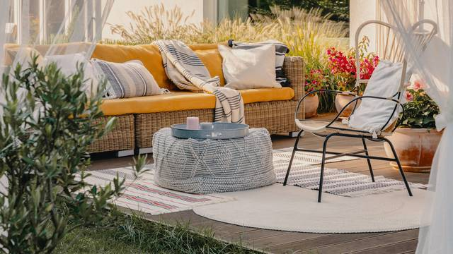 Real photo of an armchair, pouf as a table and wicker couch on a terrace