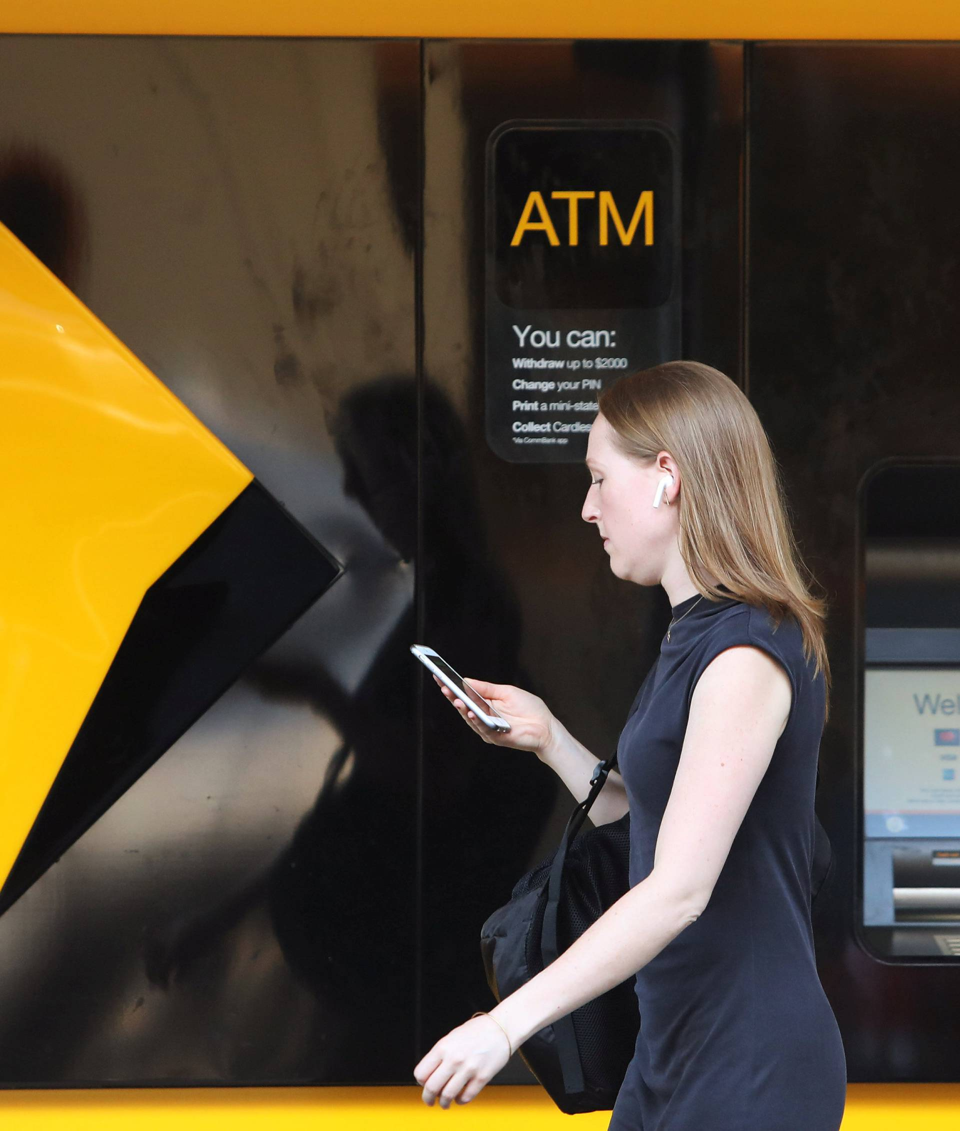 A woman walks past a Commonwealth Bank of Australia logo in Sydney