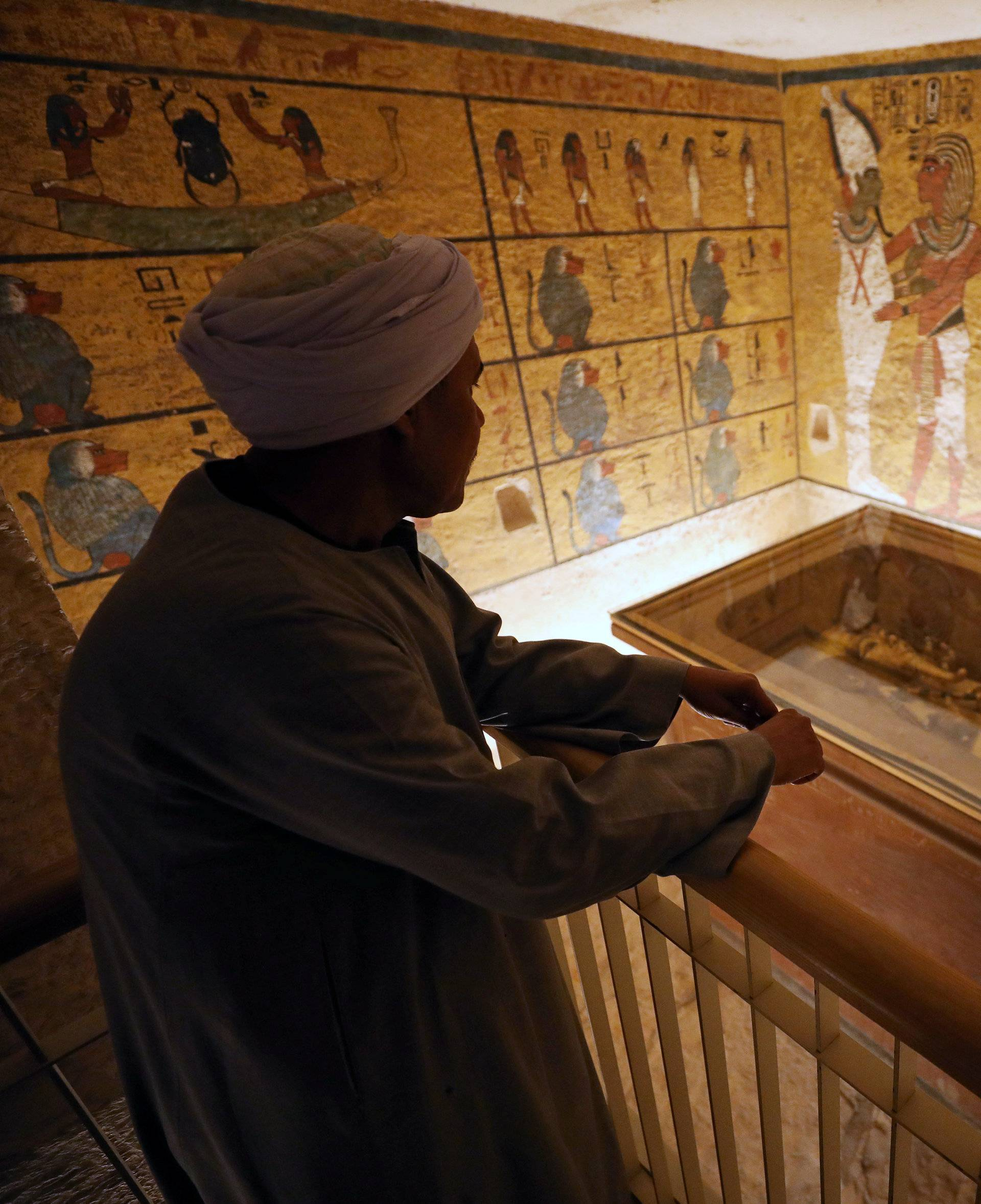 A guard looks at ancient Egyptian drawings and the sarcophagus in the newly renovated tomb wall of boy pharaoh King Tutankhamun in the Valley of the Kings in Luxor