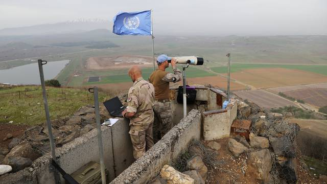 UN soldiers look out on a post at Mount Avital, in the Israeli-occupied Golan Heights near the Israeli Syrian border