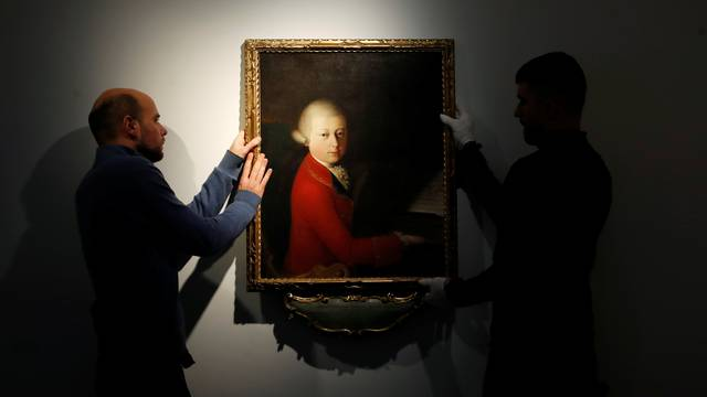 Workers install a portrait due to be sold at auction by Christie's in Paris which depicts composer Wolfgang Amadeus Mozart