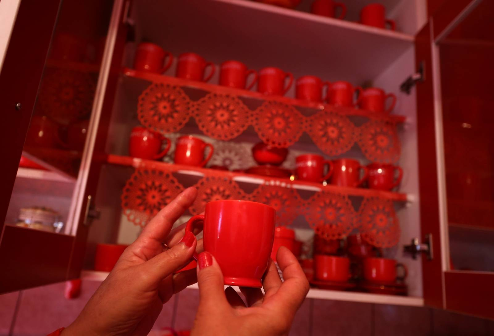 Zorica Rebernik, obsessed with the red color, holds a coffee cup in the kitchen inside her house in the village of Breze near Tuzla