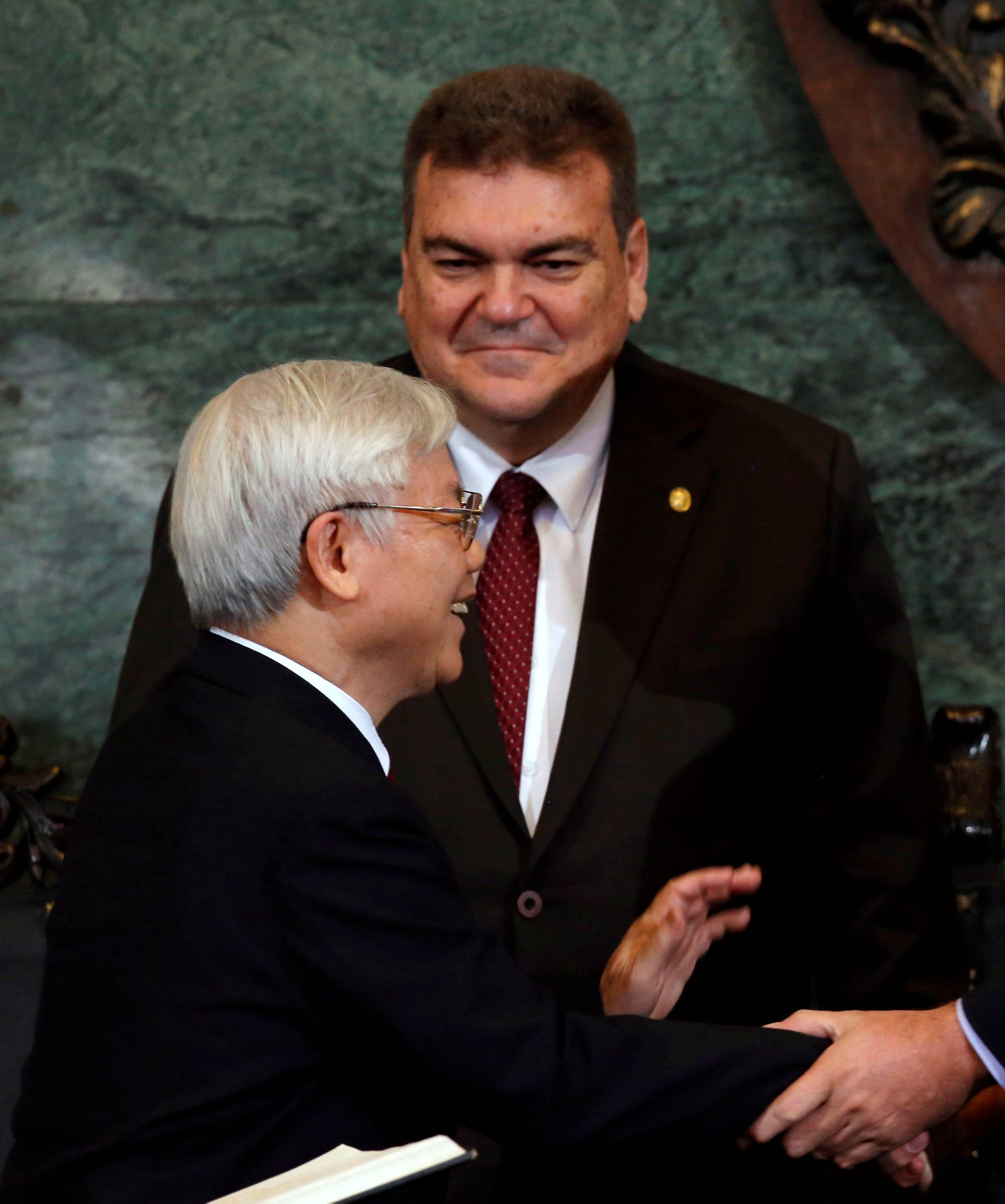 Vietnam's Communist Party Secretary General Nguyen Phu Trong shakes hands with Cuba's First Vice-President Miguel Diaz-Canel, next to Gustavo Cobreiro, rector of the University of Havana, in Havana