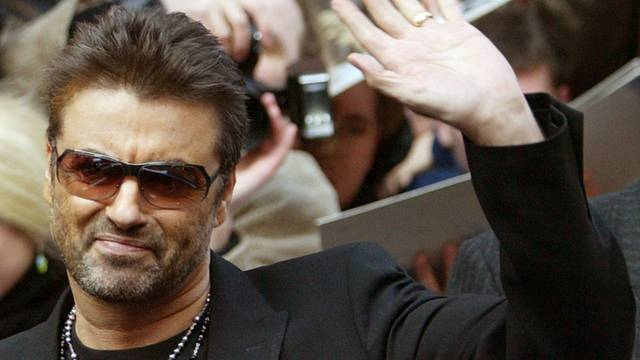FILE PHOTO: British singer and actor George Michael waves as he leaves a news conference to introduce the film 'George Michael: A Different Story'  in Berlin