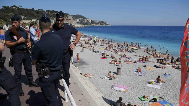 French CRS police patrol on the walkway above a public beach with sunbathers as security measures continue after the Bastille Day truck attack by a driver who ran into a crowd on the Promenade des Anglais that killed scores and injured as many, in Nice