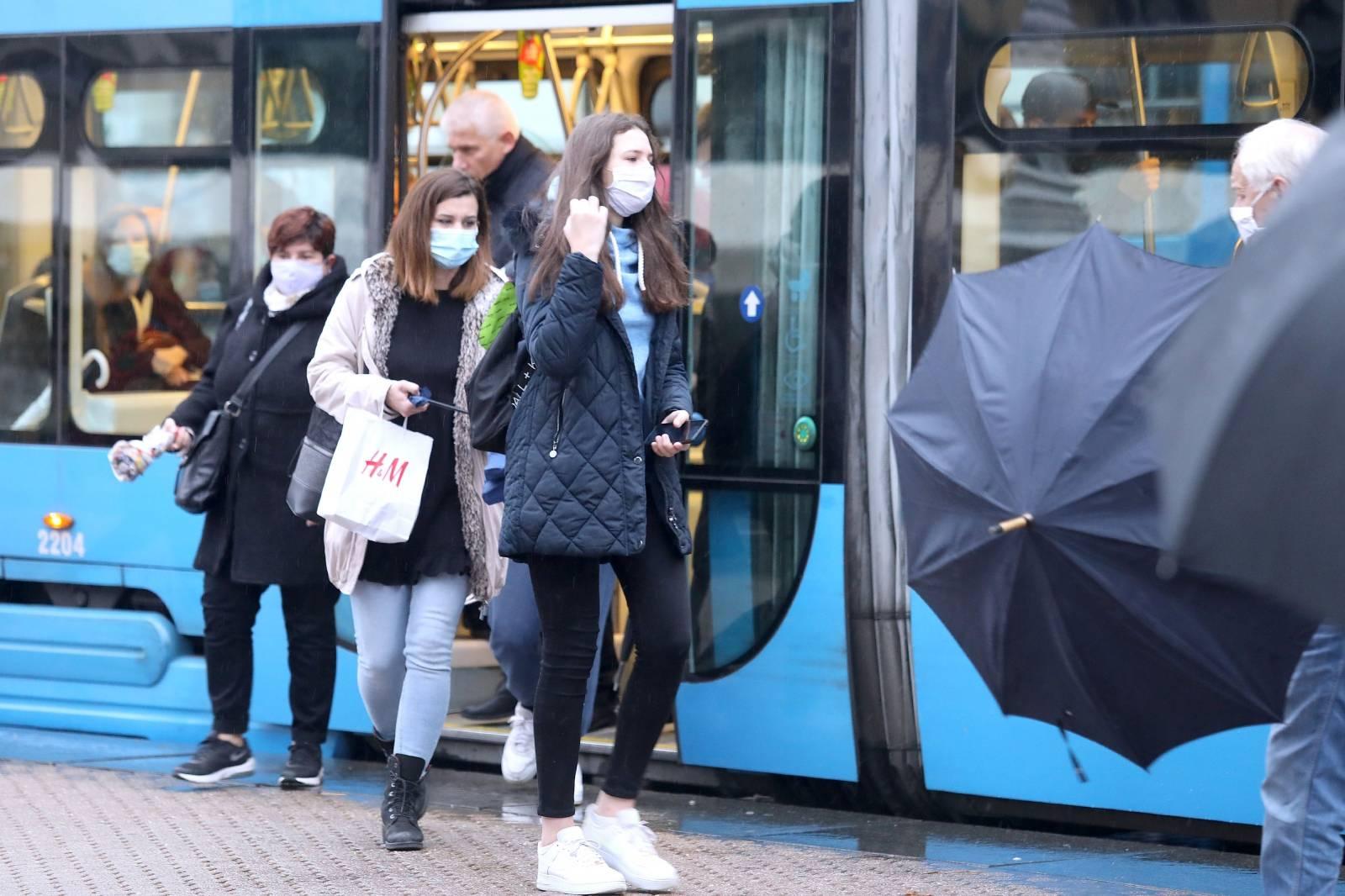 Zagreb: Građani sa zaštitnim maskama na glavnom Trgu i dok čekaju tramvaj