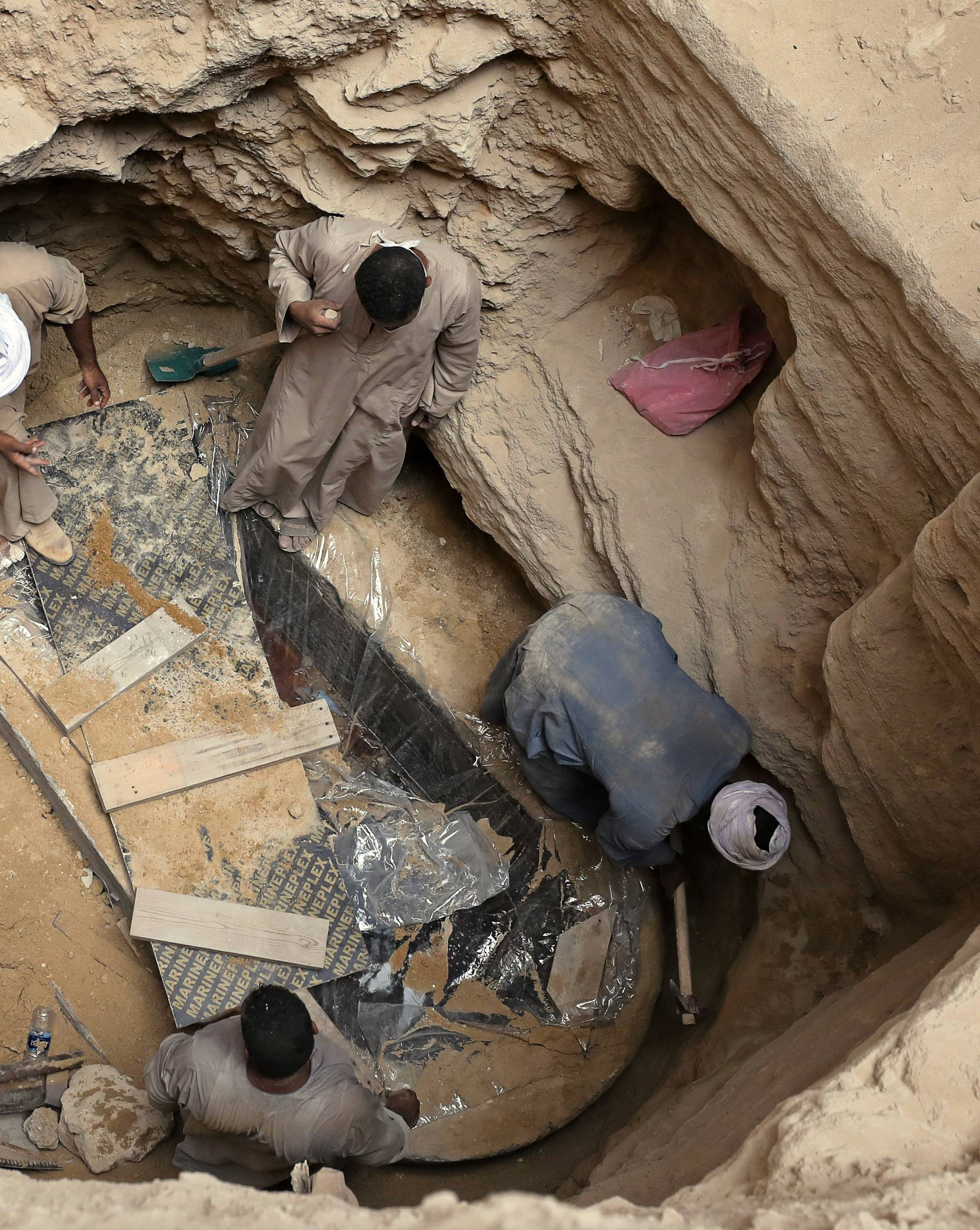 Archaeologists and workers unearth closed coffin containing three mummies with remains of three people in Alexandria