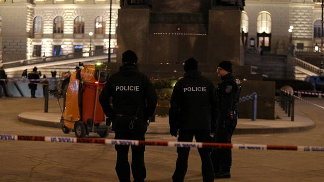 Police officers are seen at the scene where a man set himself on fire in downtown Prague