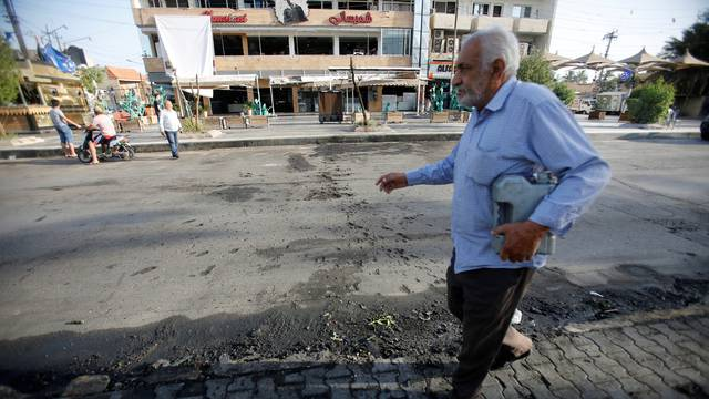 An Iraqi man walks past the site of a car bomb exploded near a cafe in Baghdad