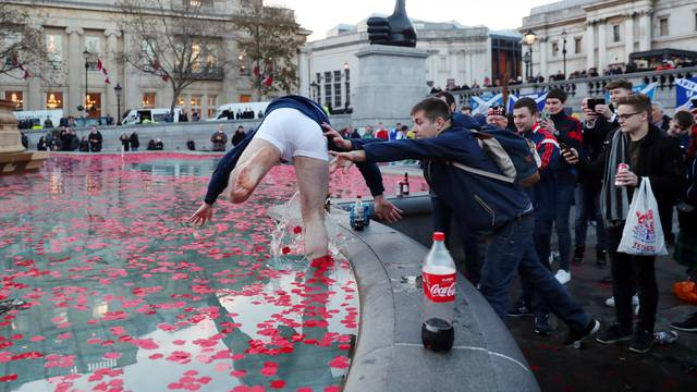 A Scotland fan in the water fountain in Trafalgar Square