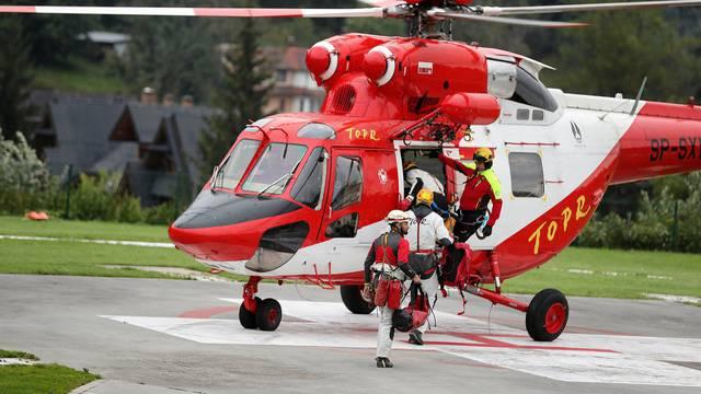 Mountain rescue team (TOPR) members board a helicopter in Zakopane