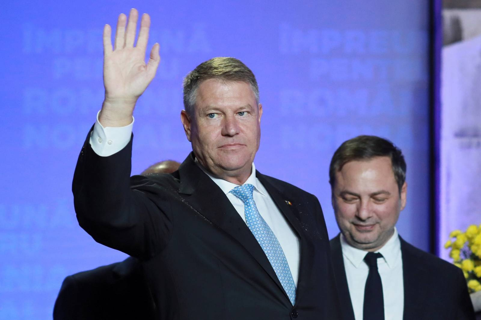 Incumbent candidate Klaus Iohannis waves during a news conference that marked the end of the first round of the presidential election, in Bucharest