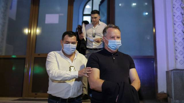 Police officers, wearing masks against the new coronavirus disease (COVID-19), escort Laurentiu Baranga, former chief of Romania's agency for the prevention and control of money laundering, to a police car