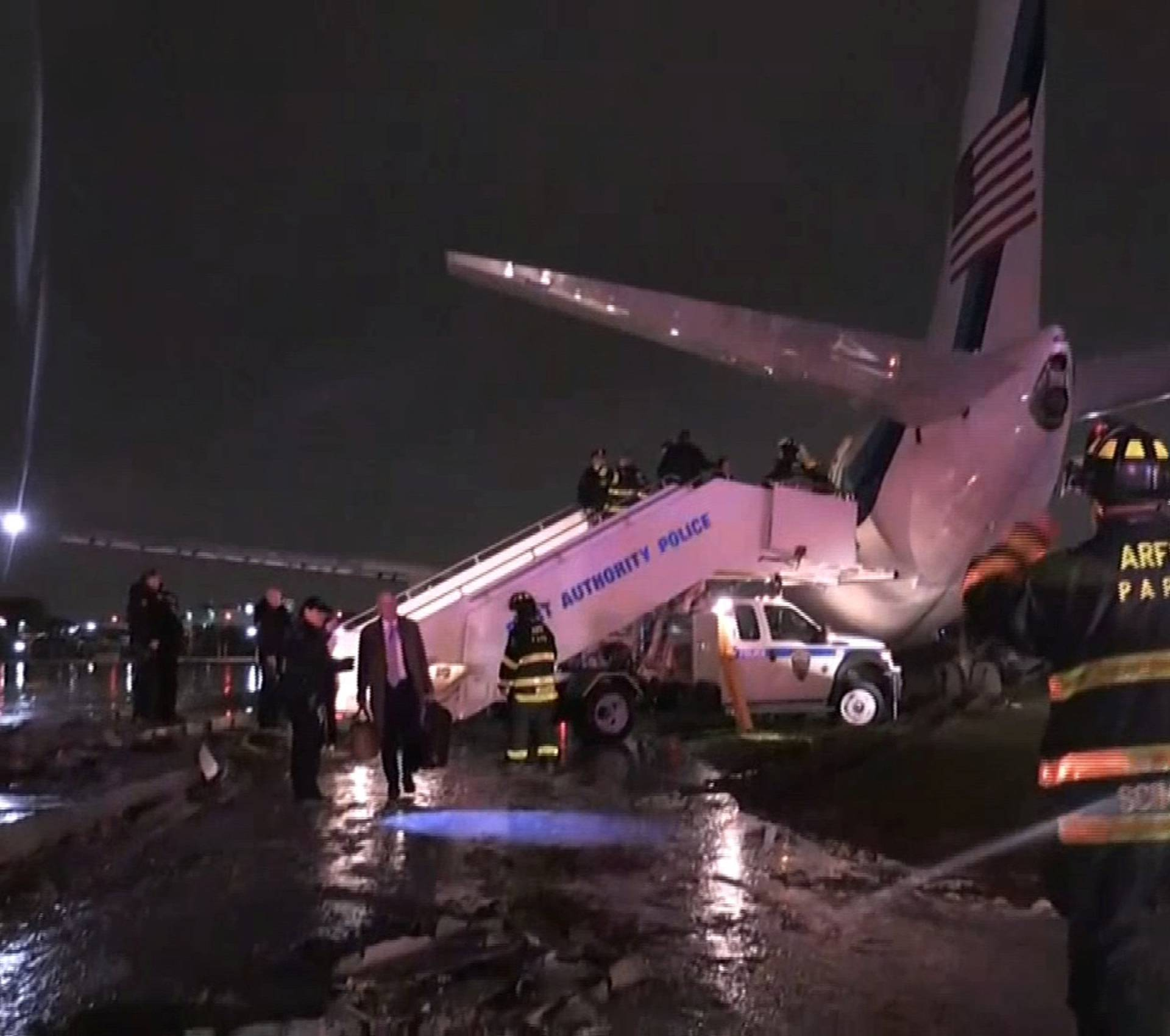 Still image of emergency workers standing in front of the plane carrying U.S. Republican vice presidential nominee Mike Pence after it skidded off the runway after landing in the rain at New York City's LaGuardia Airport