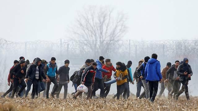 Migrants carry an injured man near the Turkey's Pazarkule border crossing with Greece's Kastanies, near Edirne