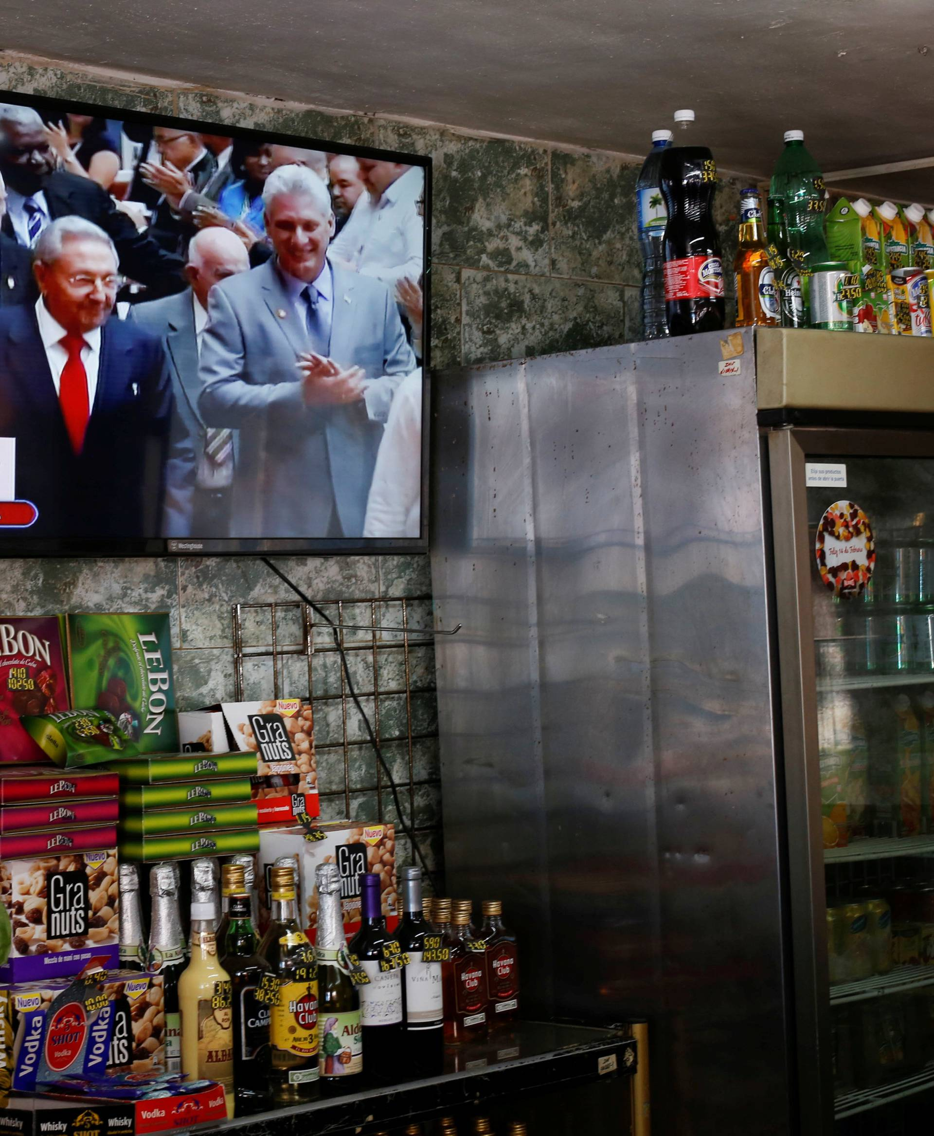 Cuba's President Raul Castro and  First Vice-President Miguel Diaz-Canel are seen on a TV screen inside a restaurant as they arrive for a session of the National Assembly in Havana