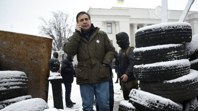 Former Georgian President Mikheil Saakashvili speaks on the phone in front of the Parliament building in Kiev