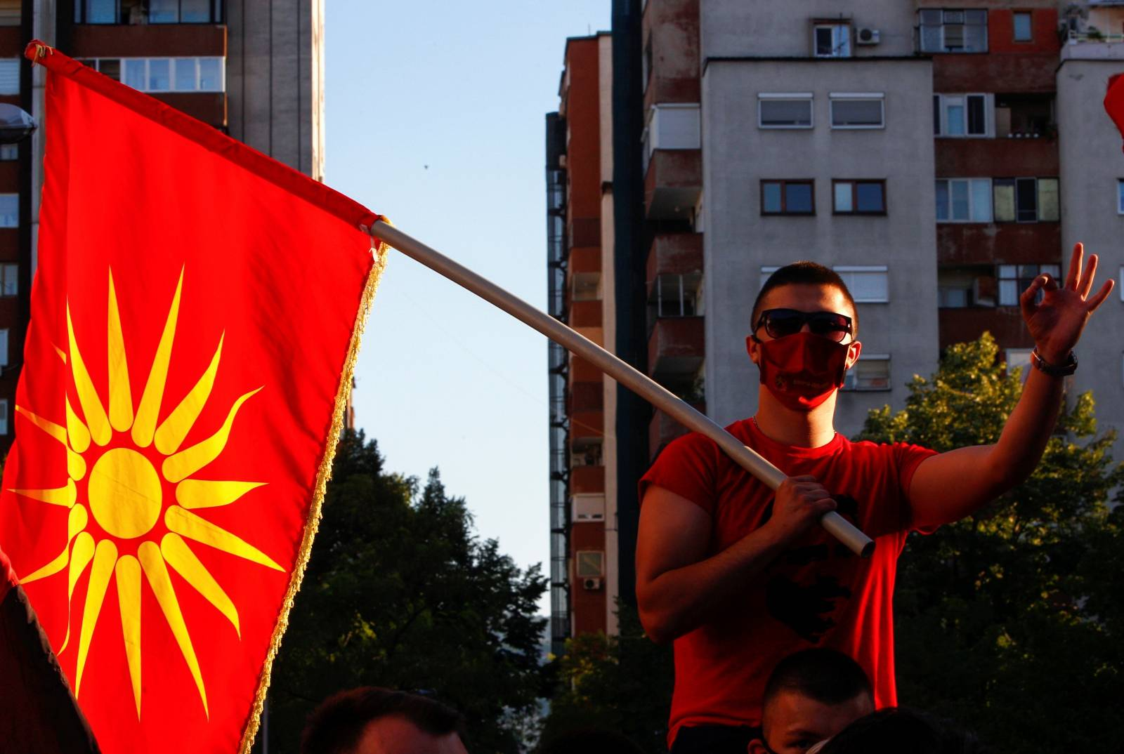 A supporter of Macedonia's nationalist opposition party VMRO-DPMNE leader Hristijan Mickoski holds a party flag during a gathering, in Skopje