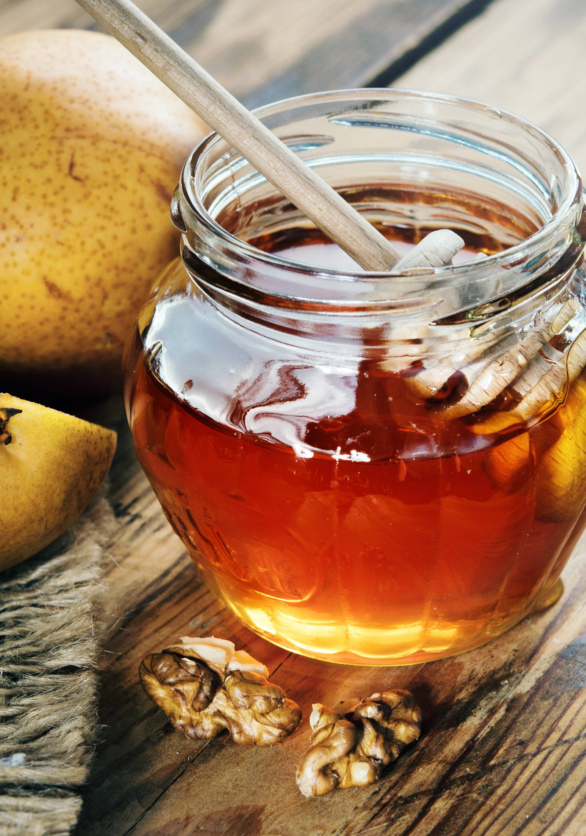 Jar of honey on a wooden table with walnuts and fruit