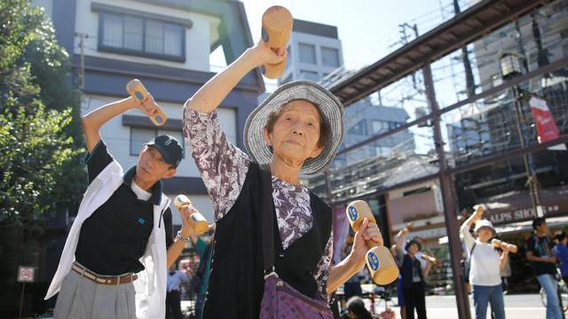 """Elderly and middle-aged people exercise with wooden dumbbells during a health promotion event to mark Japan's """"Respect for the Aged Day"""" at a temple in Tokyo's Sugamo district"""