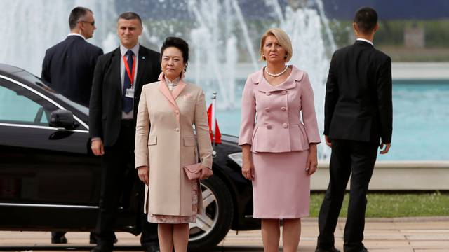 Chinese President Xi Jinping's wife Peng Liyuan (L) and Serbian President Tomislav Nikolic's wife Dragica listen to national anthems during a welcoming ceremony in Belgrade