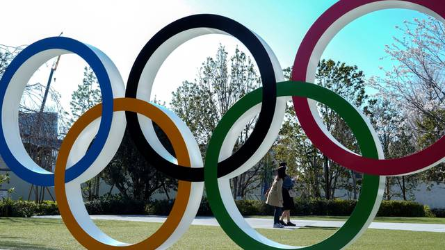 Women wearing protective face masks following an outbreak of the coronavirus disease are seen through the Olympic rings in Tokyo