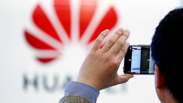 FILE PHOTO: A man takes a picture of a Huawei logo at the Huawei European Cybersecurity Center in Brussels