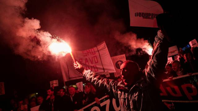 A demonstrator holds a flare during civic protest in Podgorica