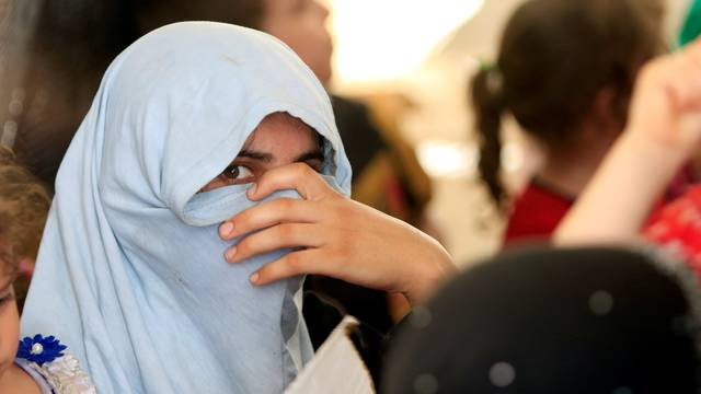 A displaced Iraqi woman who fled from Islamic State militants waits for a security check in Mosul