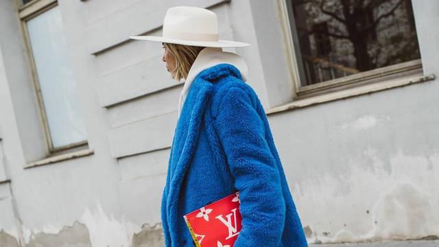 Plavi 'teddy' kaput uz bijeli elegantni šešir i crvenu torbicu