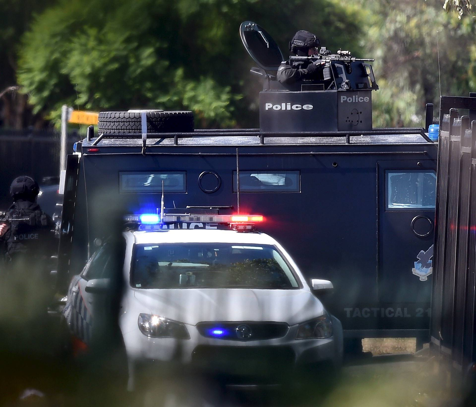 Heavily armed tactical police officers aim their weapons at the scene of a shooting in the western Sydney suburb of Ingleburn, Australia