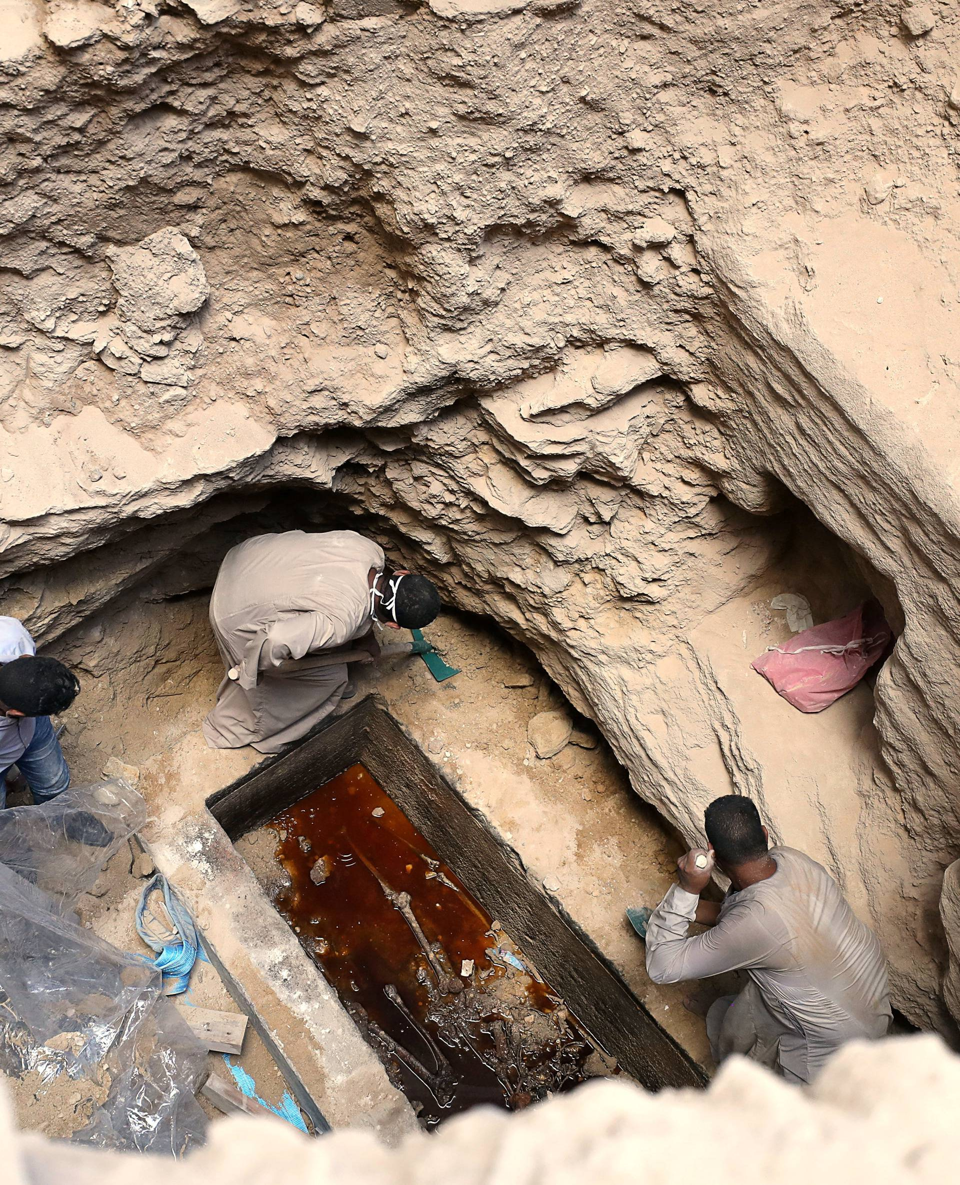 Archaeologists unearth coffin containing three mummies with sewage water and bones inside, in Alexandria