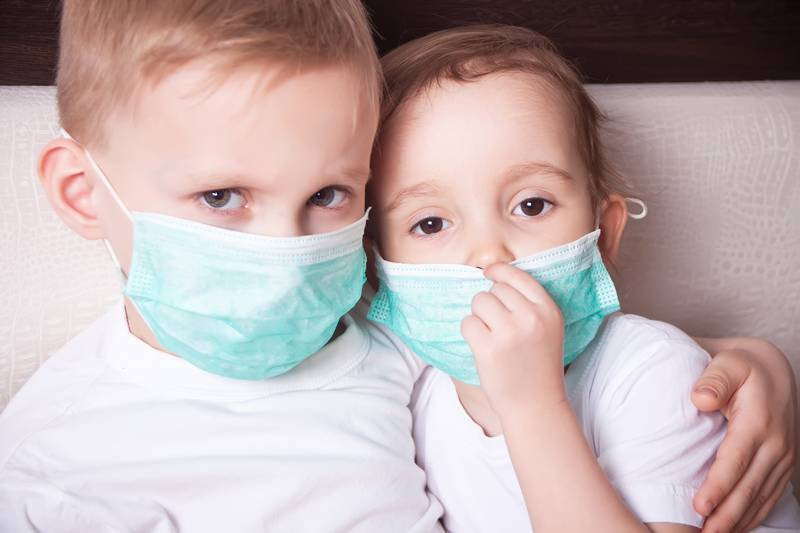 Boy and girl, a children in a medical mask. The concept of an epidemic, influenza, protection from disease, vaccination.