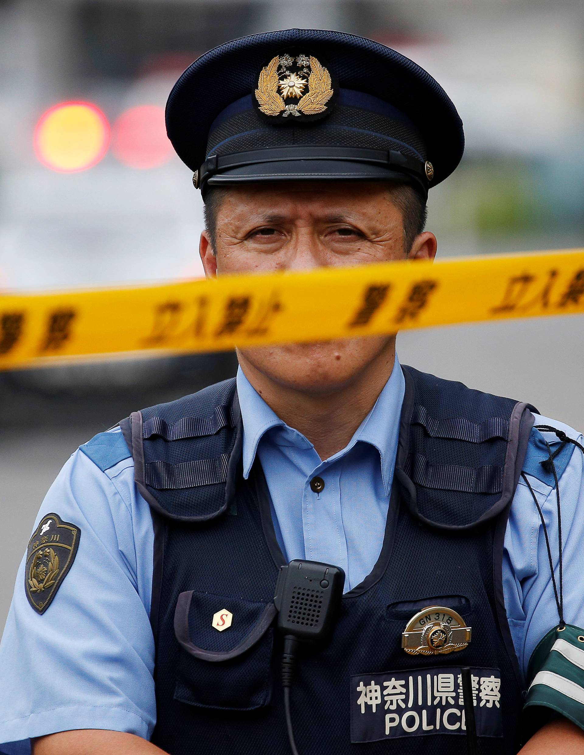 A police officer stands guard near a facility for the disabled, where a deadly attack by a knife-wielding man took place, in Sagamihara, Kanagawa prefecture, Japan