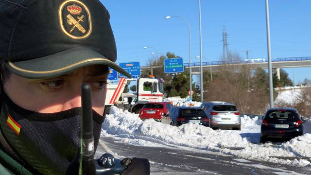 A Spanish Civil Guard talks on his walkie talkie in front of cars accumulated on M-40 highway after heavy snowfall in Madrid