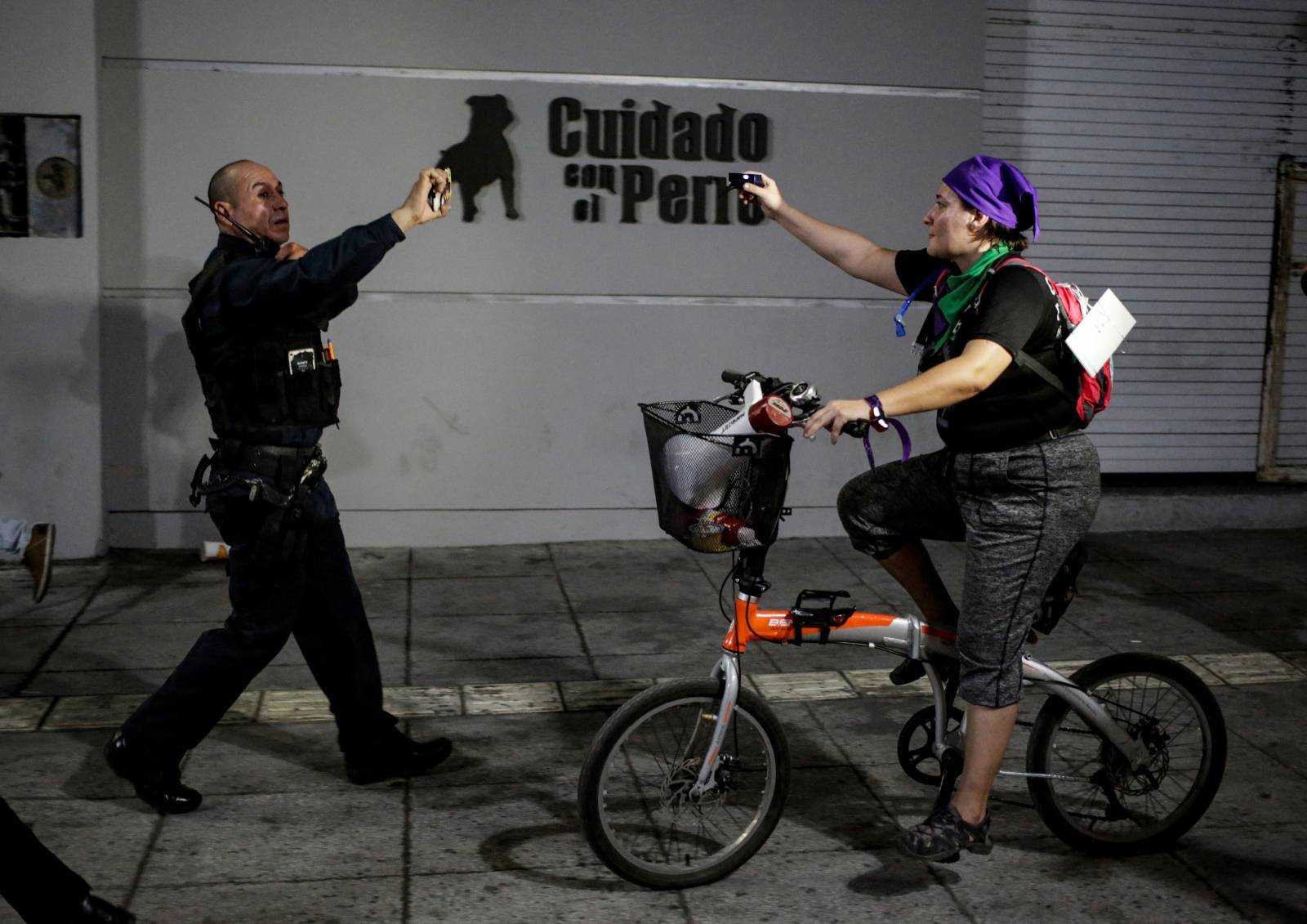 """A policeman records with his cell phone during the """"They Don't Protect Me, They Rape Me"""" demonstration in Monterrey"""