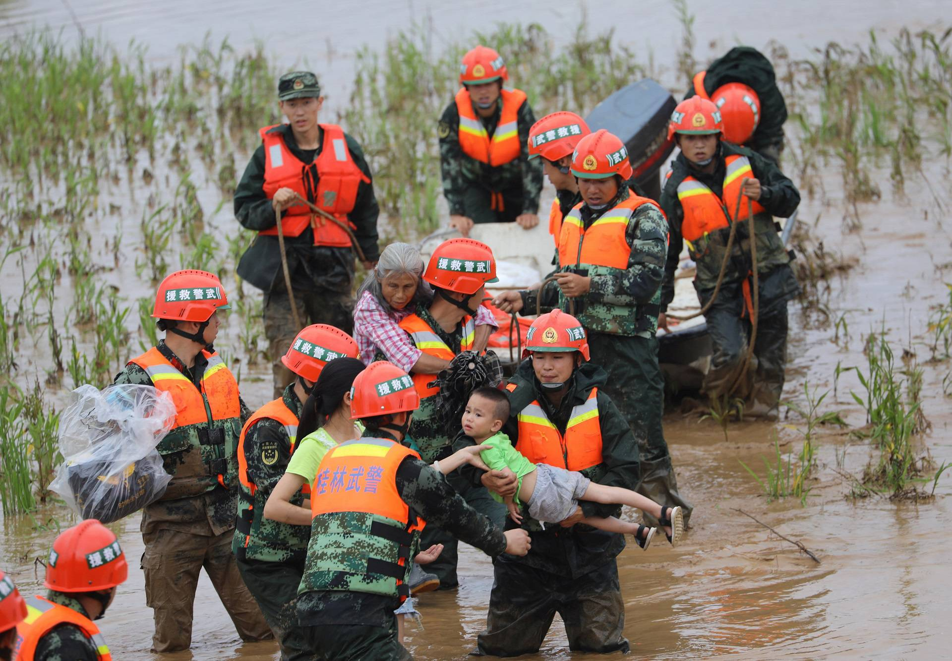 Paramilitary officers rescue stranded villagers at a flooded field in Quanzhou county, Guilin, Guangxi