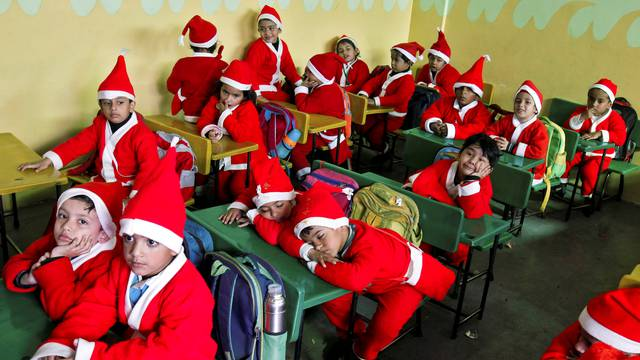Children dressed in Santa Claus costumes sit inside a classroom before participating in Christmas celebrations at a school in Chandigarh
