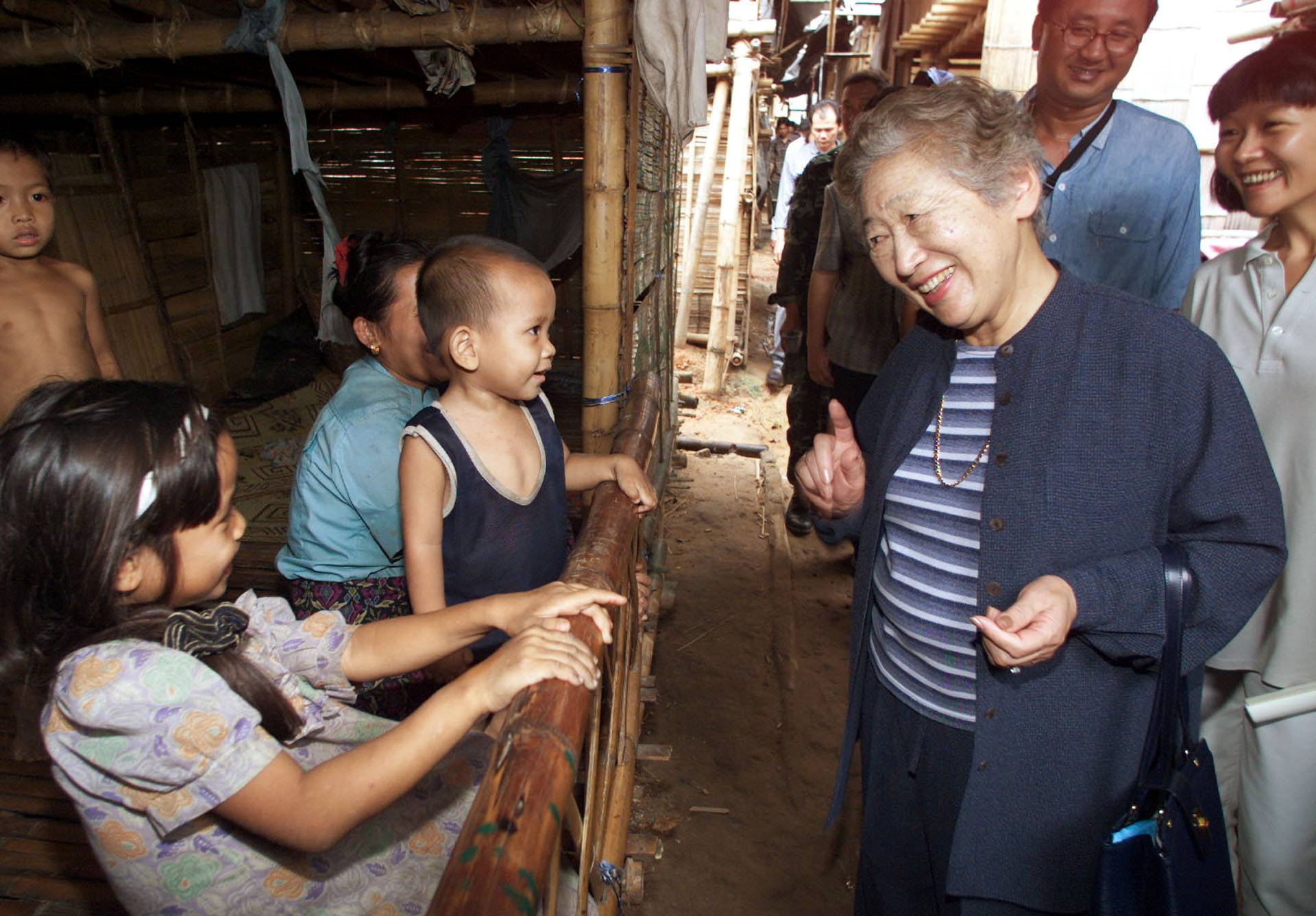 FILE PHOTO: United Nations High Commissioner for Refugees Sadako Ogata talks to a young refugee family from Myanmar at their camp in Thailand
