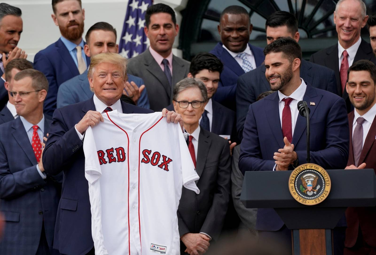 FILE PHOTO: U.S. President Donald Trump holds a Boston Red Sox jersey presented by outfielder and designated hitter J.D. Martinez while welcoming the 2018 World Series Champions on the South Lawn at the White House in Washington.