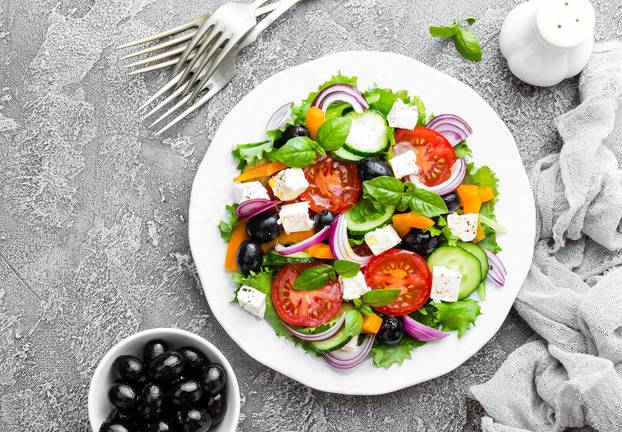 Greek salad. Fresh vegetable salad with tomato, onion, cucumbers, basil, pepper, olives, lettuce and feta cheese. Greek salad on plate