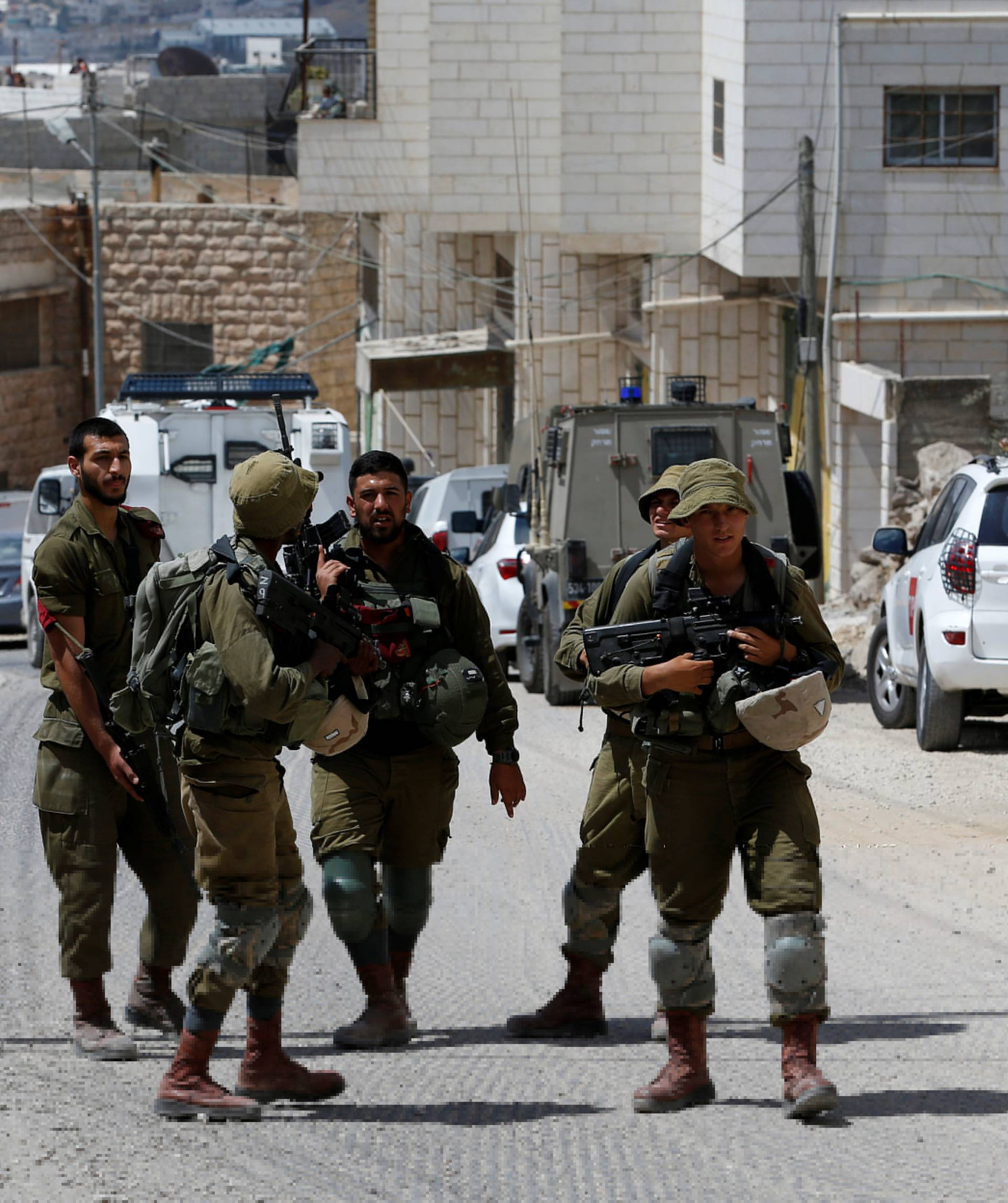 Israeli soldiers stand at the scene of attempted car ramming attack, in Hebron in the occupied West Bank
