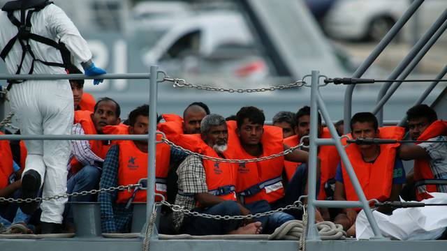 Rescued migrants are seen on board of a patrol boat as they enter Marsamxett Harbour, Valletta