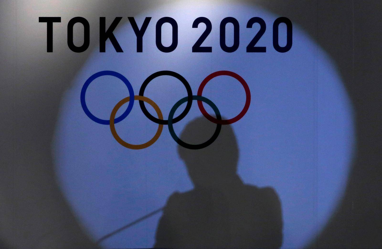 FILE PHOTO: Shadow of of Tokyo governor Yuriko Koike is seen on the logo of Tokyo 2020 Olympic games during the Olympic and Paralympic flag-raising ceremony at Tokyo Metropolitan Government Building in Tokyo