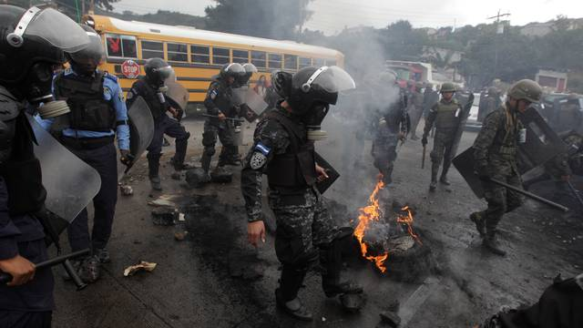 Security forces remove a burning barricade settled to block a road by supporters of Nasralla during a protest over a contested presidential election in Tegucigalpa