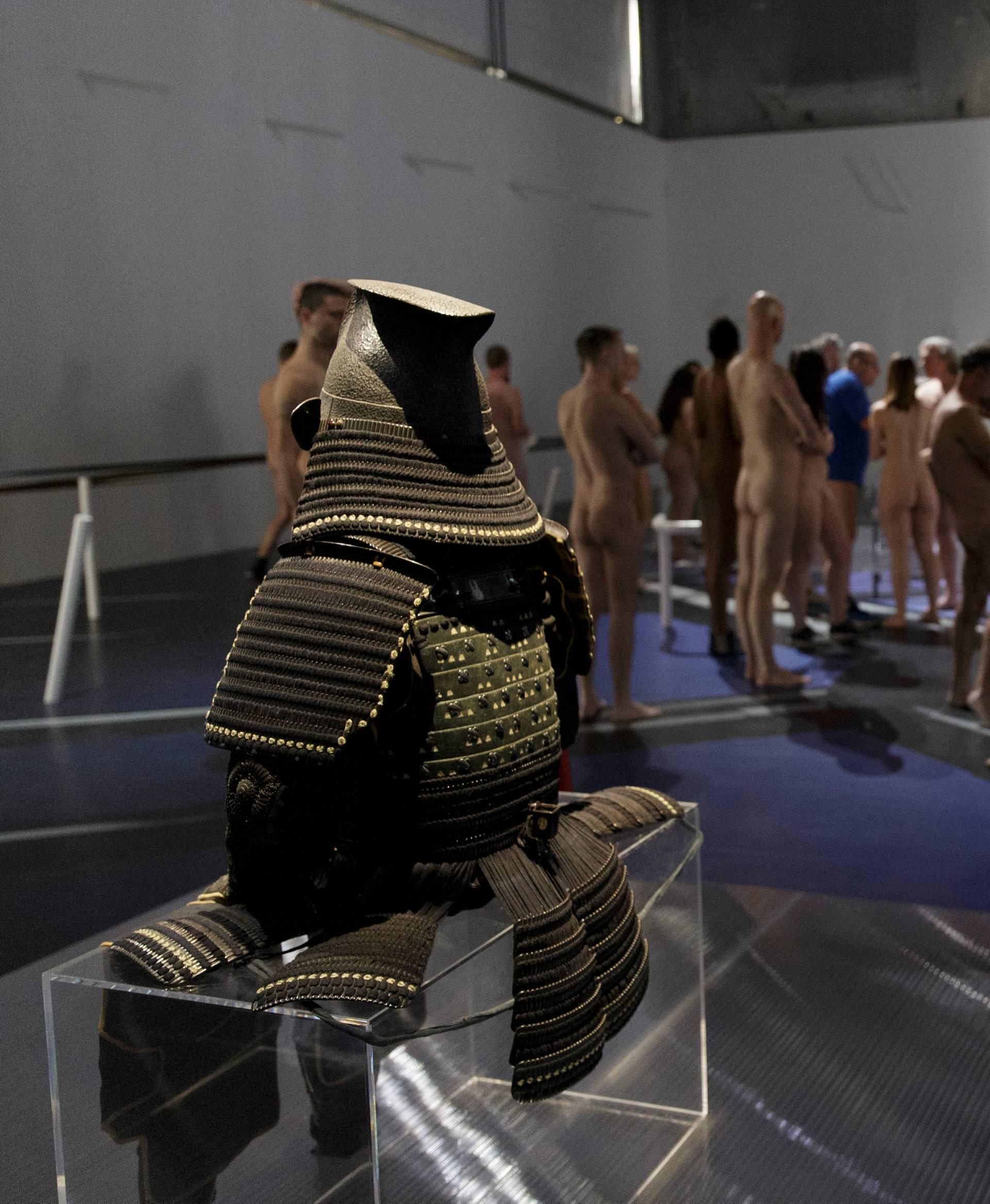 People take part in a nudist visit of the 'Discorde, Fille de la Nuit' season exhibition at the Palais de Tokyo contemporary art centre in Paris