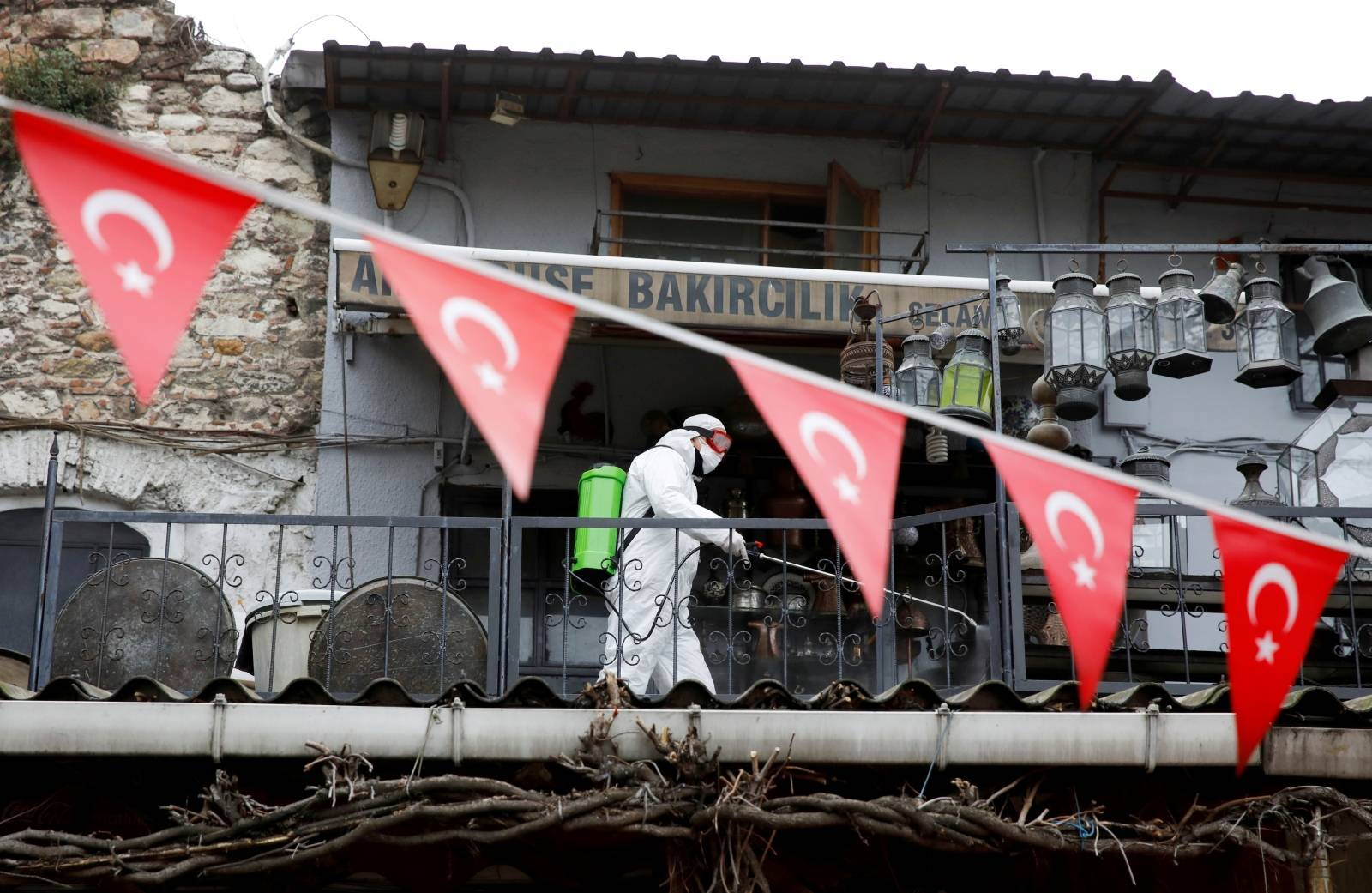 FILE PHOTO: A worker in a protective suit sprays disinfectant at Grand Bazaar, known as the Covered Bazaar, to prevent the spread of coronavirus